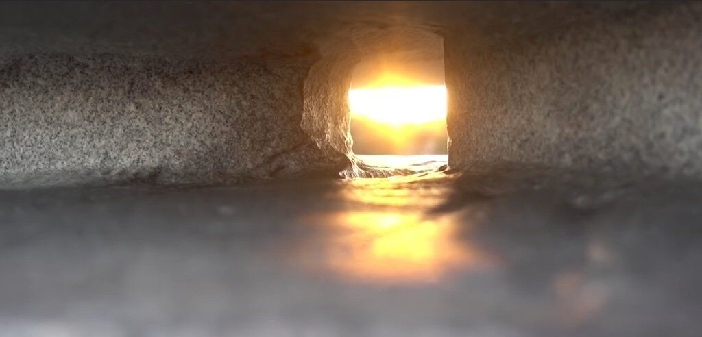 A still of Tom Scott's video below shows the slit in the column capturing the sunbeam.