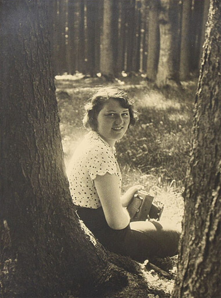 Geli Raubal posing with a camera in the woods.