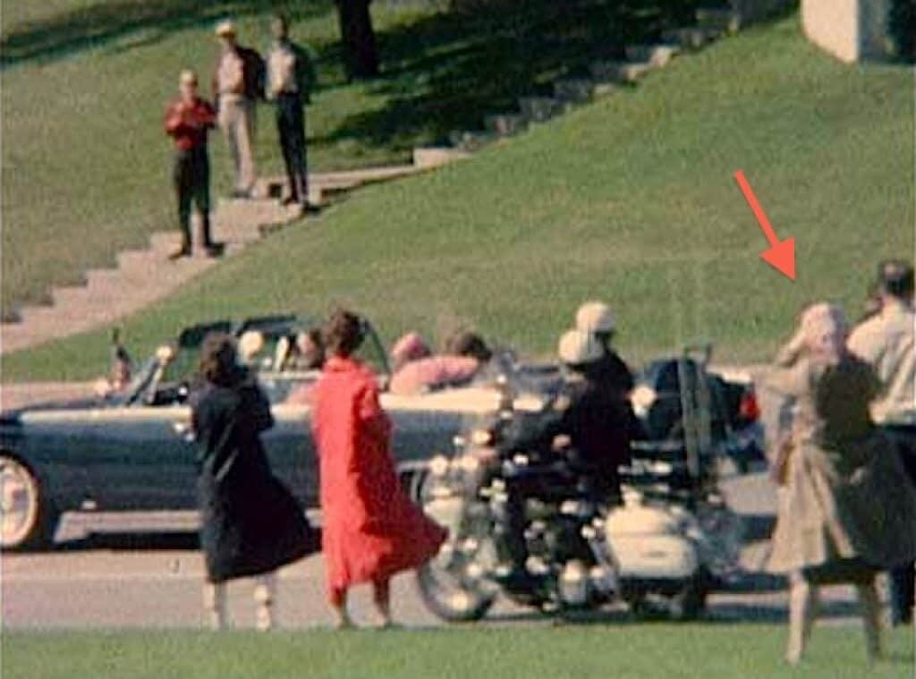 Babushka lady in tan coat and light scarf appears to be holding a camera to her face as Kennedy goes by.