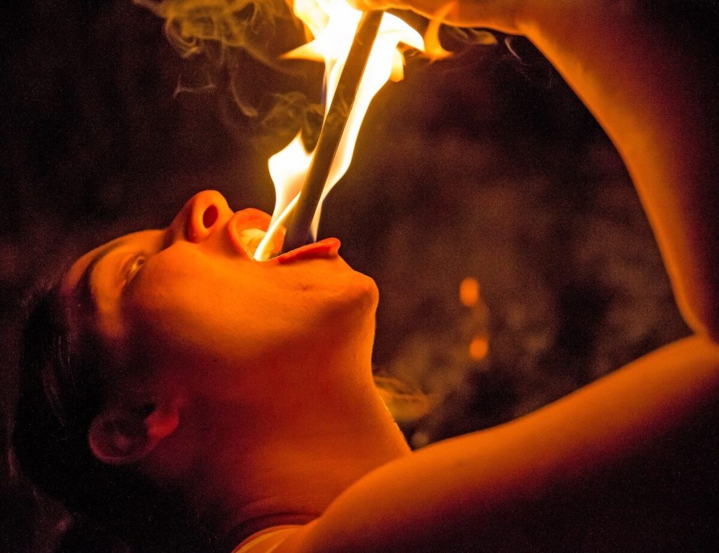Skilled like Jo Girardelli, Sword-swallower Samantha Jones places a fire wand in her mouth. Image: Jayson Mellom.