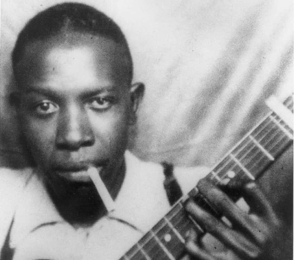 Robert Johnson holding his guitar.