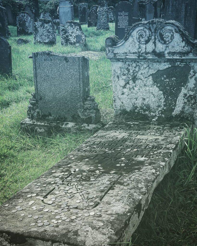Coins left on Robert Kirk's grave at Aberfoyle Churchyard.