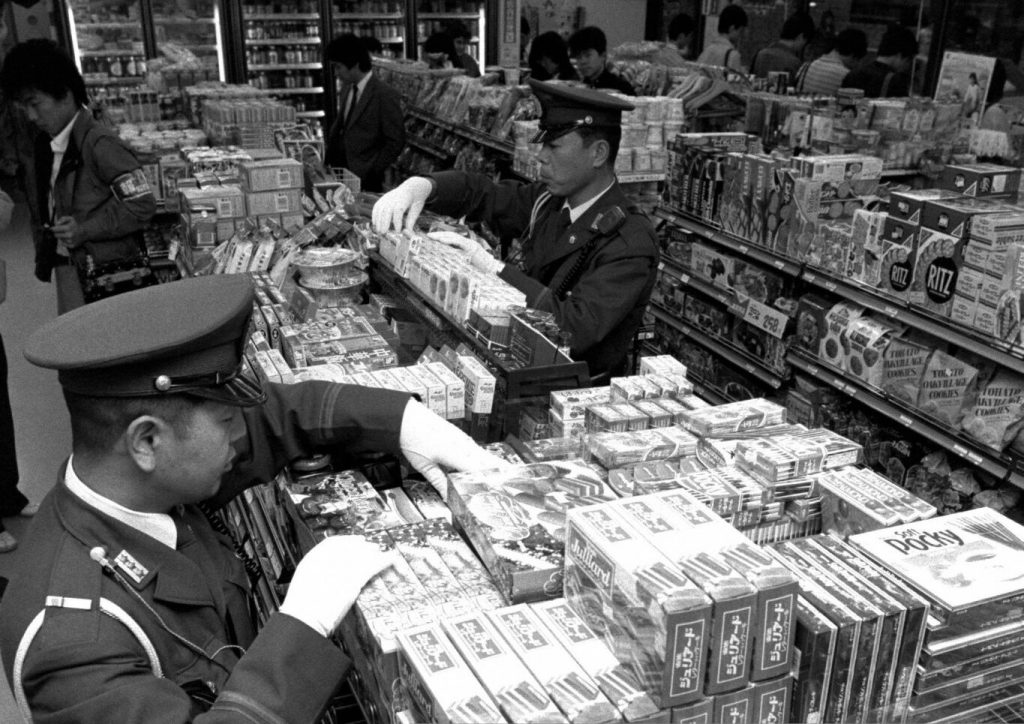 Police officers check Morinaga products on the shelf at a convenience store on October 26, 1984 in Tokyo, Japan.