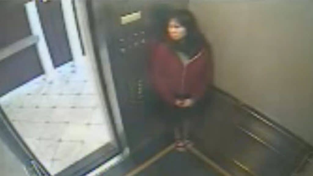 CCTV picture frame of of the elevator footage. It appears as if she is hiding from someone.