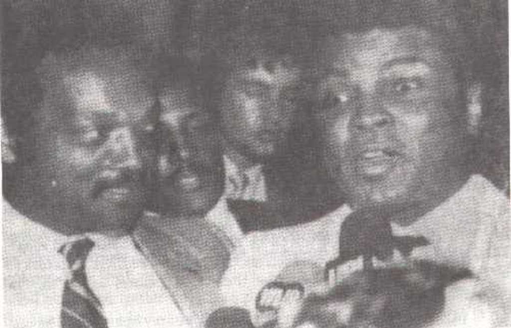 A 1984 image of Jesse Jackson and Muhammad Ali. A person resembling Elvis Presley can be seen in the background.