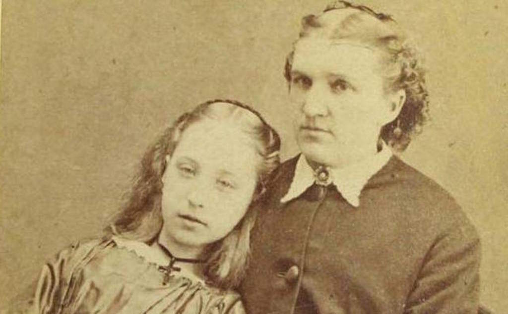A woman poses with her deceased child.