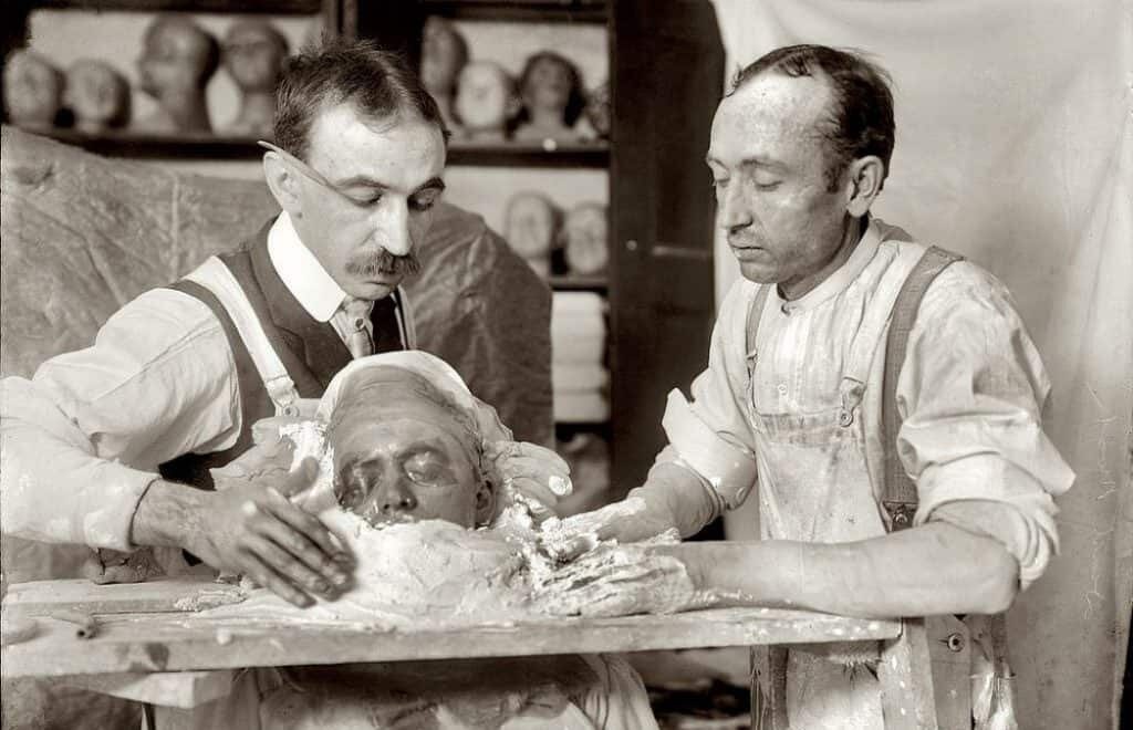 Two men are in the process of making a death mask from a deceased man. Wikimedia Commons, public domain.