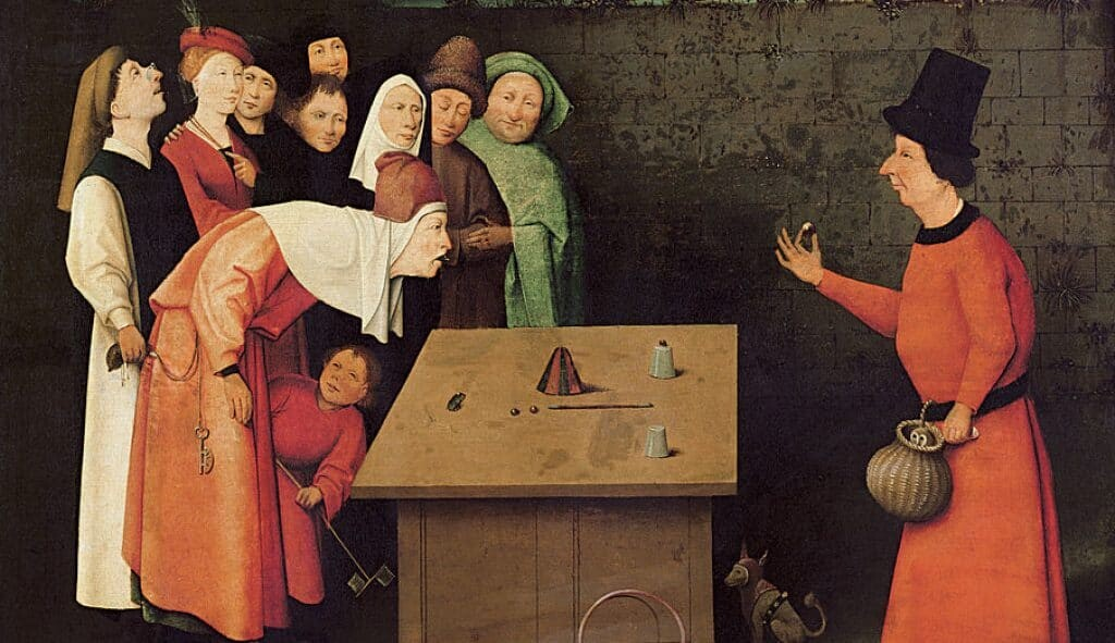 A magician performs a cup trick while a man steals the money purse of a spectator, c 1475, <em>The Conjurer</em> by Hieronymus Bosch.