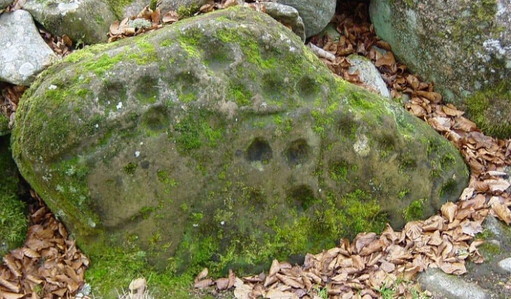 Cup marks in a passage-type Clava cairn. Public domain.