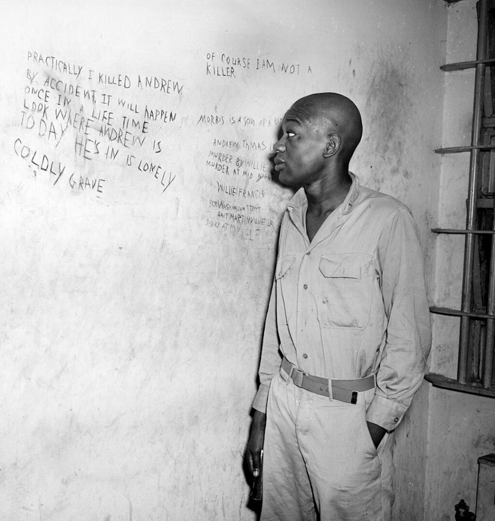 Willie viewing the writing on the prison wall. His head is shaved in preparation for the electric chair.